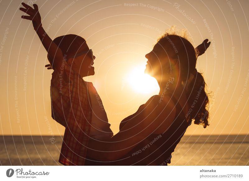 Mutter und Sohn spielen zur Zeit des Sonnenuntergangs am Strand. Die Menschen haben Spaß im Freien. Konzept eines glücklichen Urlaubs und einer freundlichen Familie.