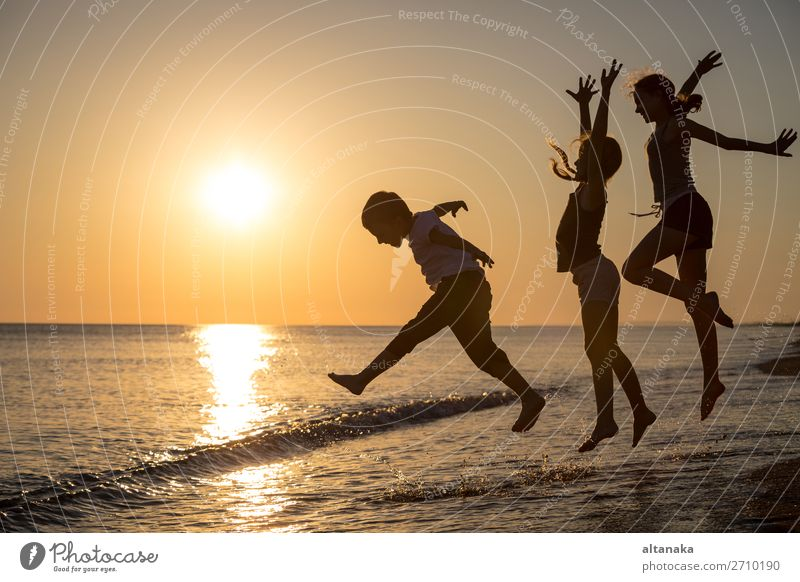Glückliche Kinder, die bei Sonnenuntergang am Strand spielen. Lifestyle Freude Freizeit & Hobby Spielen Ferien & Urlaub & Reisen Ausflug Abenteuer Freiheit