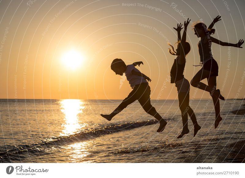 Glückliche Kinder, die zur Zeit des Sonnenuntergangs am Strand spielen. Drei Kinder, die sich im Freien vergnügen. Konzept der Sommerferien und einer freundlichen Familie.