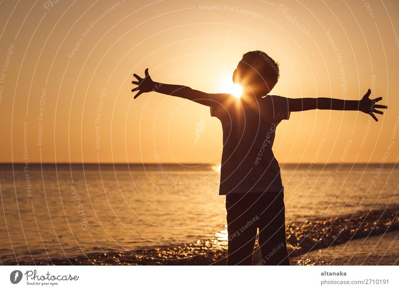 Ein glücklicher kleiner Junge, der zur Zeit des Sonnenuntergangs am Strand spielt. Ein Kind, das Spaß im Freien hat. Konzept der Sommerferien. Lifestyle Freude
