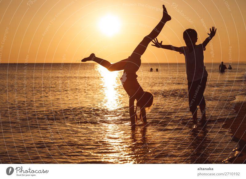 Glückliche Kinder, die zur Zeit des Sonnenuntergangs am Strand spielen. Zwei Kinder, die sich im Freien vergnügen. Konzept der Sommerferien und einer freundlichen Familie.