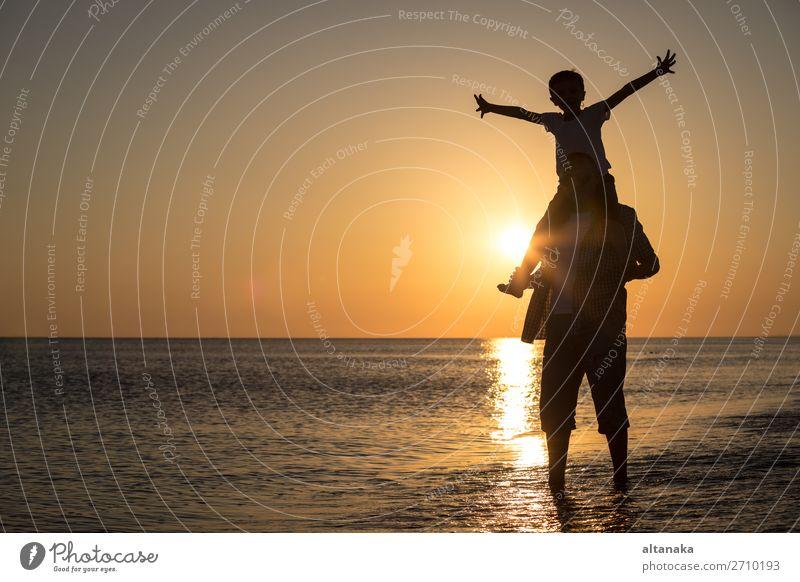 Vater und Sohn spielen zur Zeit des Sonnenuntergangs am Strand. Die Menschen haben Spaß im Freien. Konzept eines glücklichen Urlaubs und einer freundlichen Familie.
