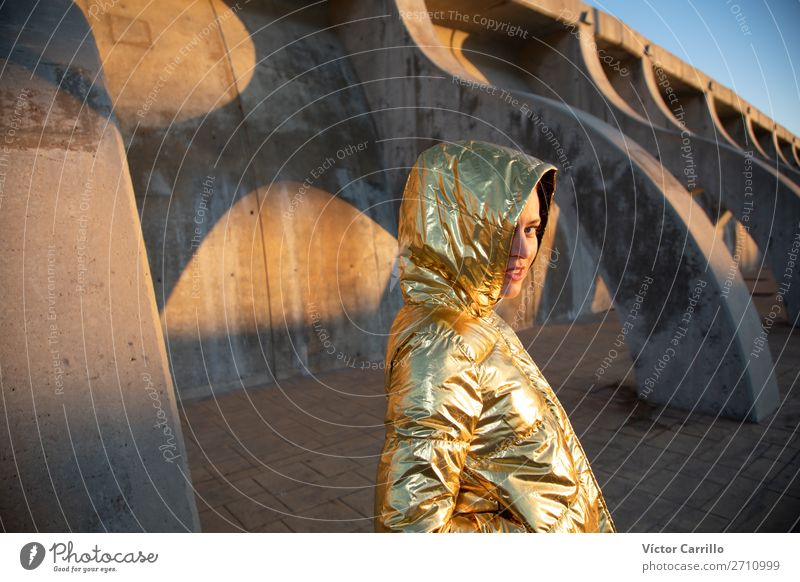 Junge Frau in einem Sonnenuntergangsfoto mit goldener Jacke Lifestyle kaufen Mensch feminin Jugendliche Erwachsene Lippen Hafenstadt Mode Bekleidung Lächeln