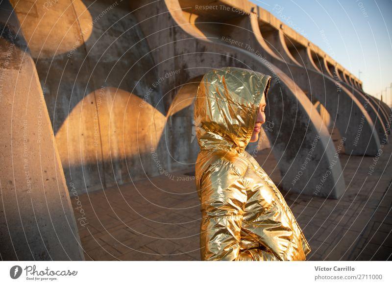 Junge Frau in einem Sonnenuntergangsfoto mit goldener Jacke Lifestyle kaufen Reichtum elegant Stil Design exotisch Freude Mensch feminin Jugendliche Erwachsene
