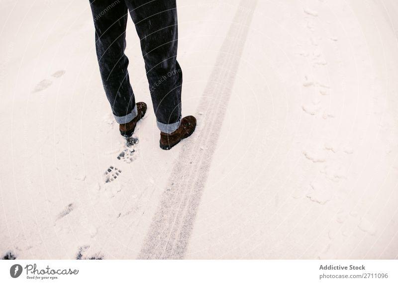 Stehende Person auf verschneiter Straße Schnee Winter Asphalt Spur Beine stehen Mensch Natur kalt Landschaft weiß Jahreszeiten Frost Tag gefroren Ausflug