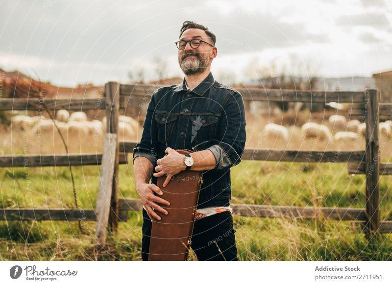 Erwachsener Mann mit Gitarrenkoffer Natur Musiker fallen stehen Wegsehen ländlich Zaun Lifestyle Mensch Sommer lässig akustisch gutaussehend Typ