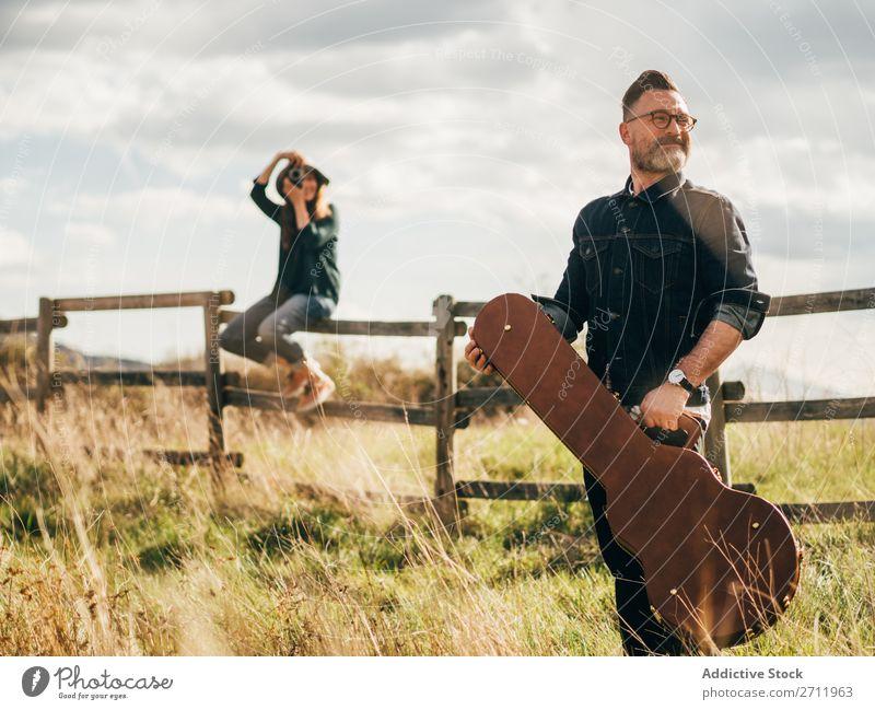 Frau, die mit der Gitarre einen Mann fotografiert. Natur Musiker Fotograf fallen sitzen ländlich Zaun Lifestyle Mensch Sommer lässig akustisch gutaussehend Typ