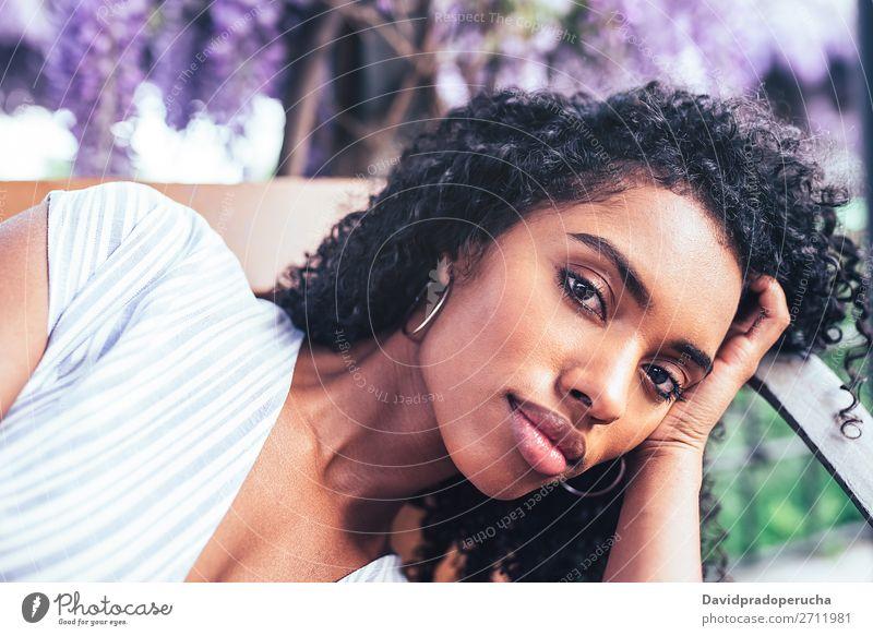 Junge schwarze Frau, die sich auf einen Stuhl legt, umgeben von Blumen. Blüte Frühling Fliederbusch Porträt multiethnisch Afrikanisch