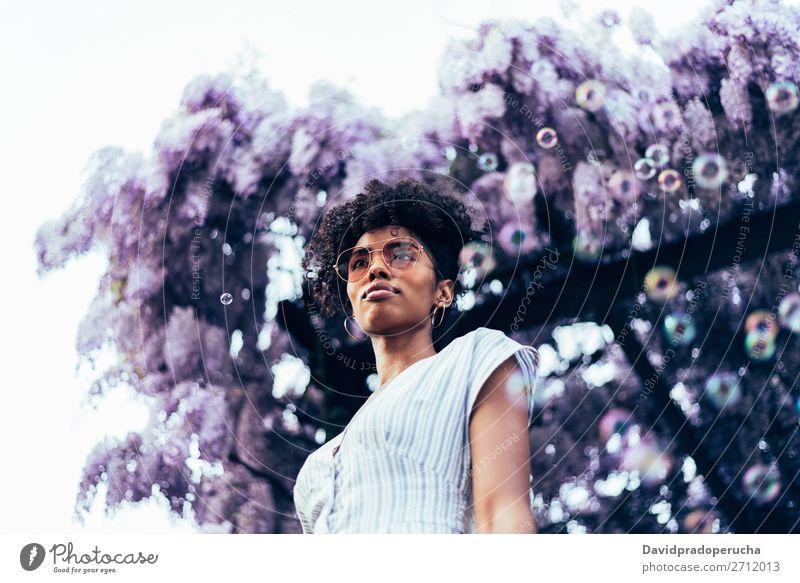 Fröhliche junge schwarze Frau, umgeben von Blumen. Blüte Frühling Fliederbusch Porträt multiethnisch Afrikanisch Person gemischter Abstammung Lächeln Wegsehen