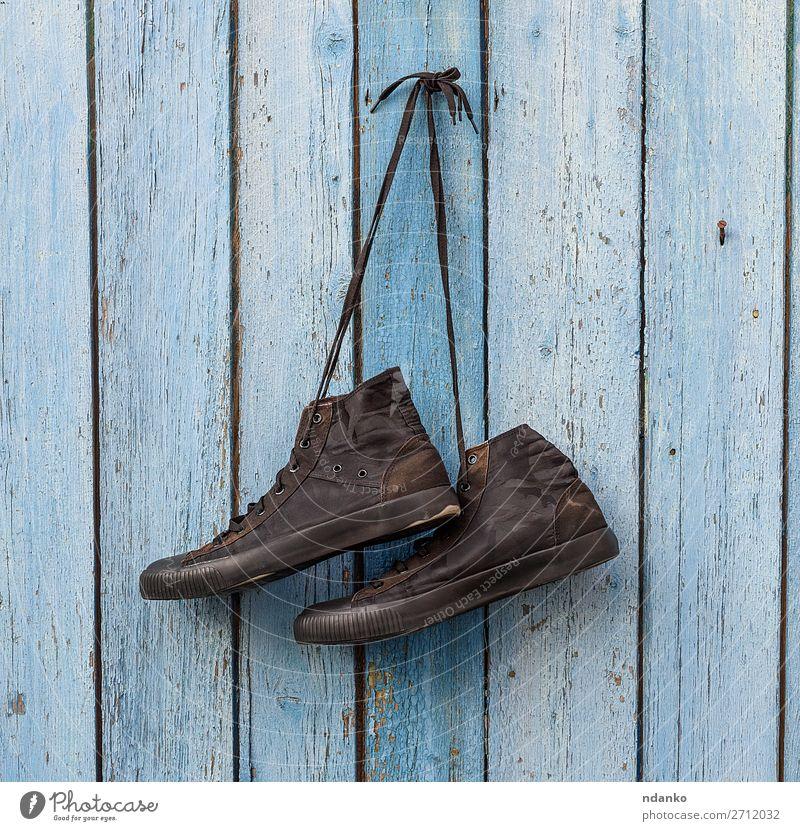 Paar schwarze Textilsneakers Lifestyle Stil Sport Joggen Mode Bekleidung Schuhe Turnschuh Holz alt hängen dreckig modern retro blau Hintergrund Holzplatte