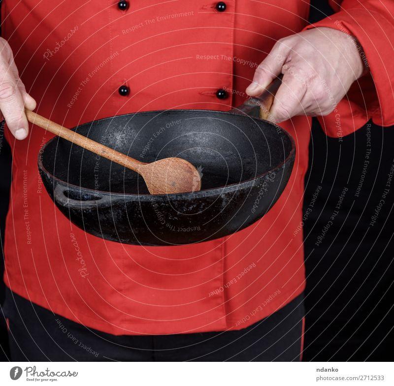 in roter Uniform kochen und eine leere schwarze Bratpfanne halten. Pfanne Löffel Küche Restaurant Beruf Koch Mensch Mann Erwachsene Hand Bekleidung Gußeisen