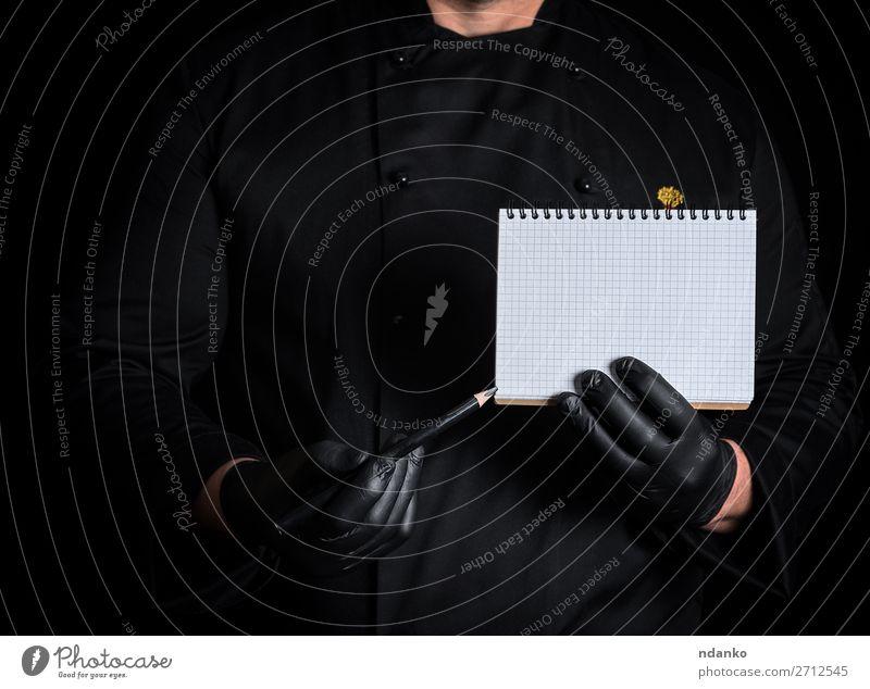 Koch in schwarzer Uniform, der ein leeres Notizbuch hält. elegant Küche Restaurant Arbeit & Erwerbstätigkeit Beruf Mensch Mann Erwachsene Hand Bekleidung Hemd