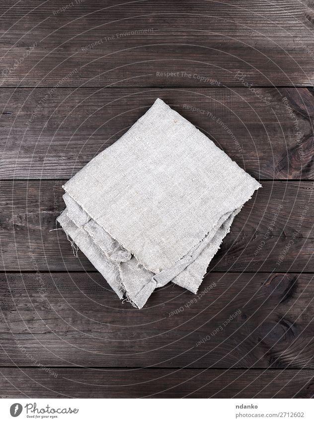 gefaltetes graues Handtuch auf braunem Holzgrund Design Tisch Küche Stoff retro Sauberkeit Serviette Hintergrund Tischwäsche Leinen Konsistenz Baumwolle Raum