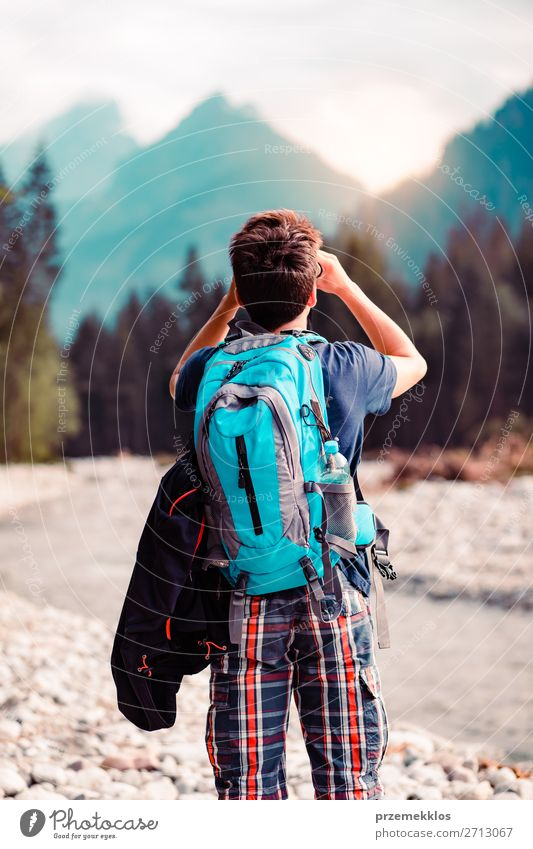 Junger Wanderer mit Rucksack schaut durch ein Fernglas. Lifestyle Leben Freizeit & Hobby Ferien & Urlaub & Reisen Tourismus Ausflug Abenteuer Sommer