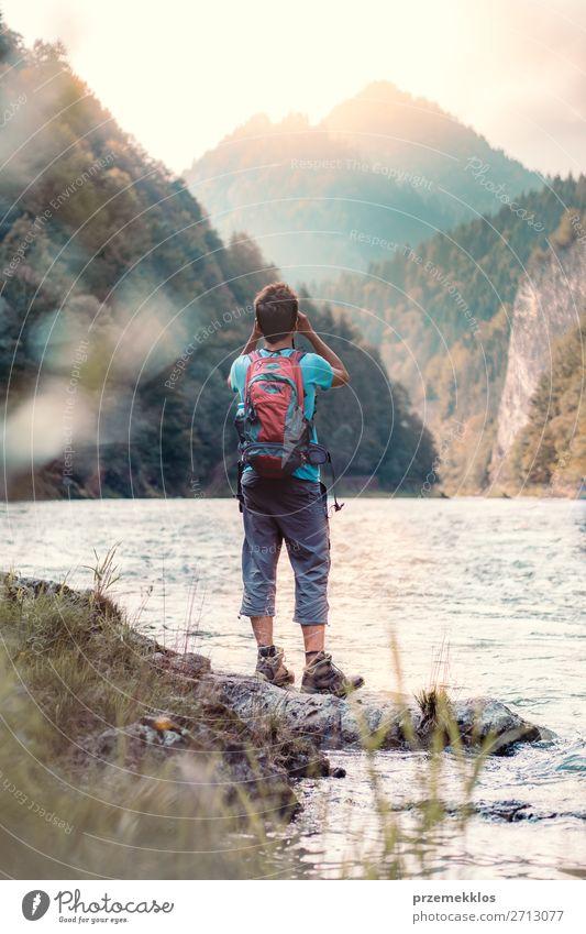 Junger Tourist mit Rucksack schaut durch ein Fernglas. Lifestyle Leben Freizeit & Hobby Ferien & Urlaub & Reisen Tourismus Ausflug Sommer Sommerurlaub