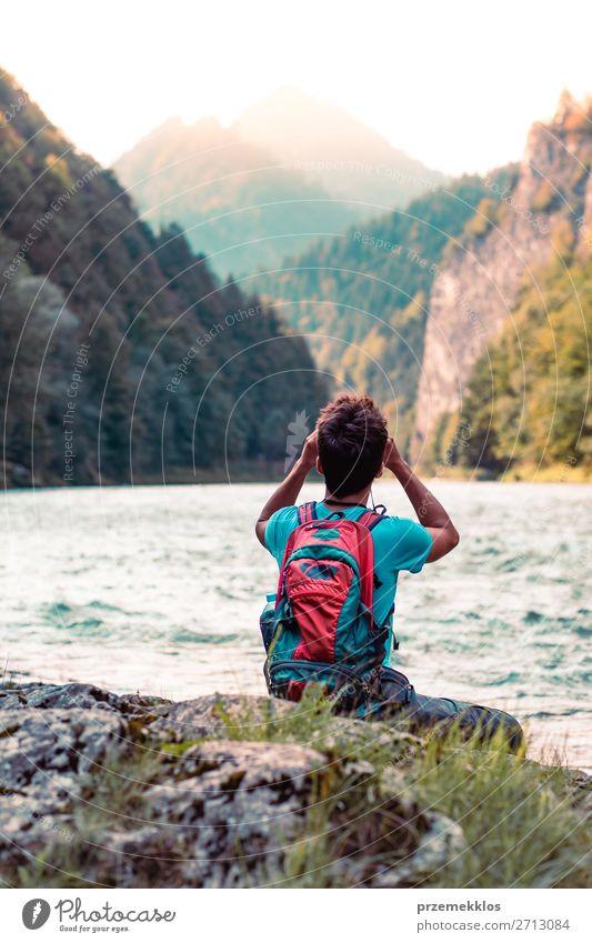Junger Tourist mit Rucksack schaut durch ein Fernglas. Lifestyle Leben Freizeit & Hobby Ferien & Urlaub & Reisen Ausflug Sommer Berge u. Gebirge Mensch