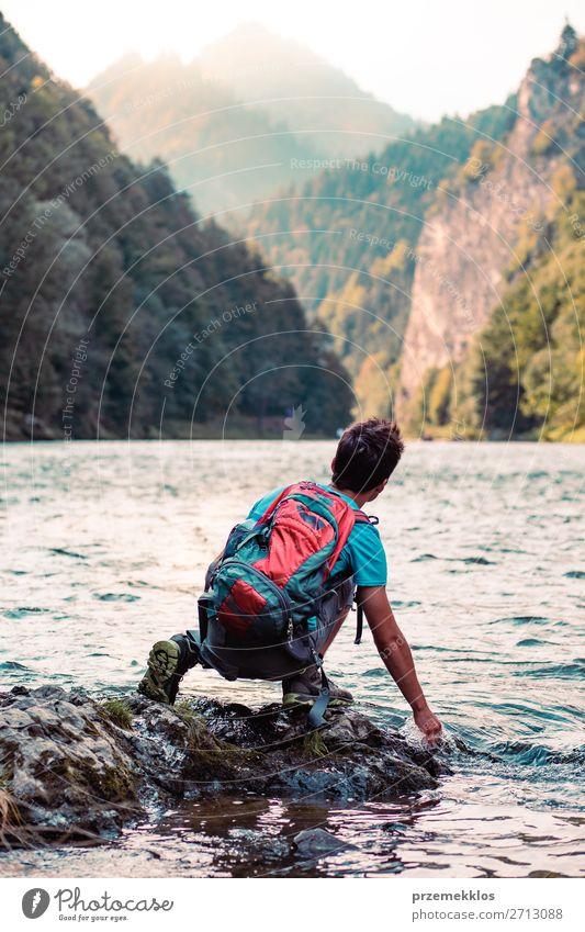 Kleiner Junge mit Rucksack, der auf einem Felsen über einem Fluss sitzt. Lifestyle Körper Leben Freizeit & Hobby Ferien & Urlaub & Reisen Ausflug Sommer