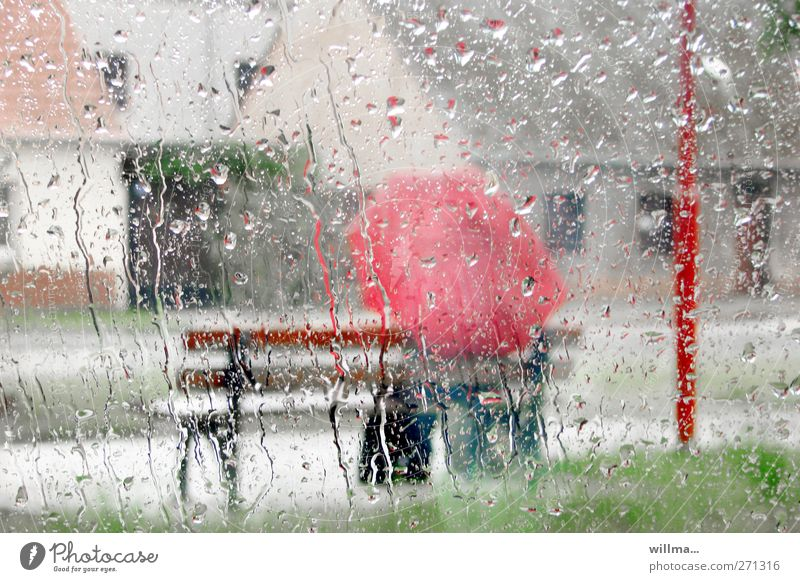 Bei Regenwetter mit Regenschirm auf der Bank chillen sitzen Mensch Wassertropfen Wetter schlechtes Wetter nass rot Fensterscheibe Glas Rinnsal Einsamkeit trist
