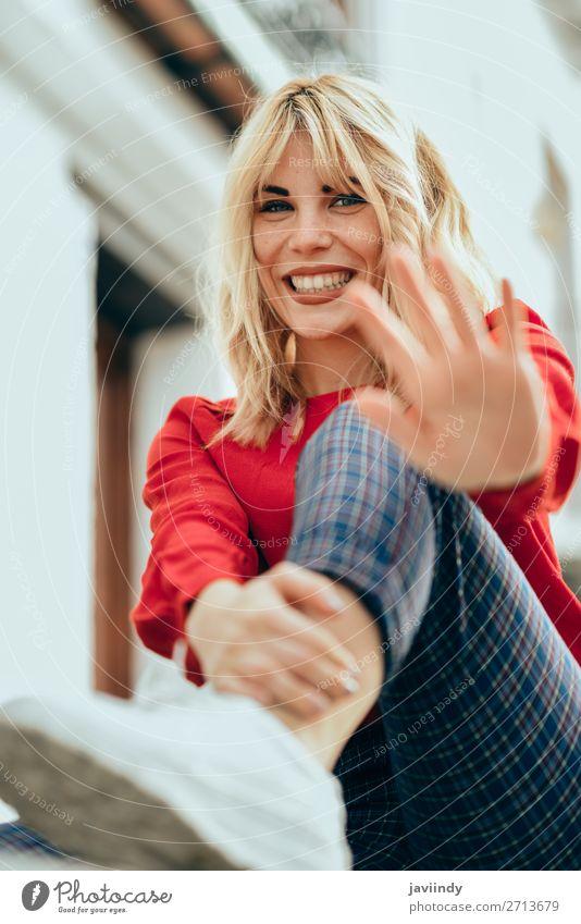 Glückliche Frau, die im Freien sitzt und ihre Hand in die Nähe der Kamera legt. Lifestyle Stil schön Haare & Frisuren Mensch feminin Junge Frau Jugendliche
