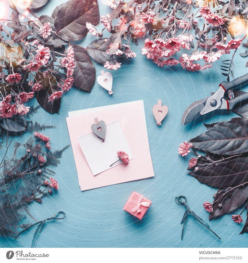 Blanko-Grußkarte auf blauem Floristenschreibtisch mit rosa Blumen, Herzen und Geschenkbox. blanko Blumenhändler Schreibtisch Kasten abstrakt Konzept Muttertag
