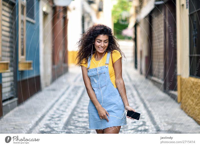 Junge arabische Frau beim Musikhören mit Kopfhörern im Freien Lifestyle Stil Glück schön Haare & Frisuren Telefon PDA Technik & Technologie Mensch feminin