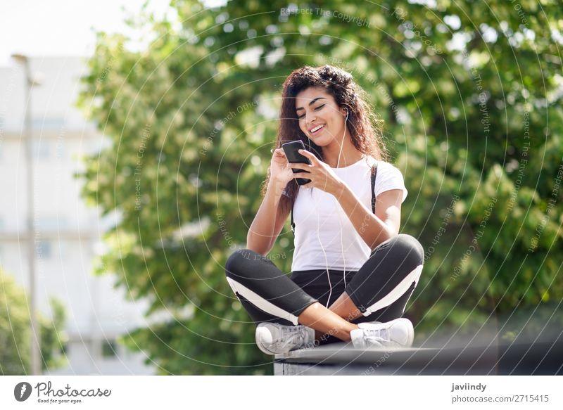 Afrikanische Frau beim Musikhören mit Kopfhörern und Smartphone Lifestyle Stil Glück schön Haare & Frisuren Sport Telefon PDA Technik & Technologie Mensch