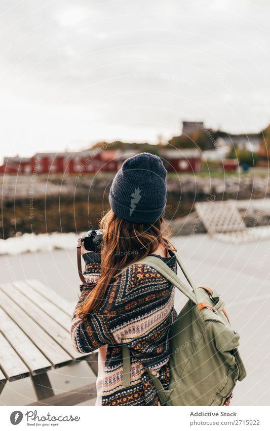 Frau mit Rucksack und Kamera Fotokamera Mensch Tourist Natur Fotografie Wohnsiedlung