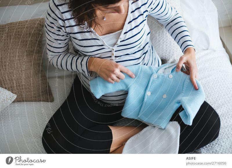Schwangere Frau beim Vorbereiten der Babykleidung Glück Körper Erholung Freizeit & Hobby Junge Erwachsene Eltern Mutter Bekleidung Pullover sitzen klein