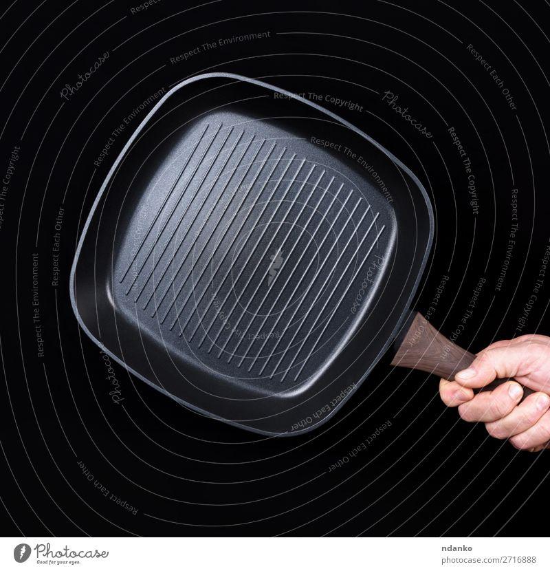 Hand hält eine schwarze, leere, quadratische Grillpfanne. Pfanne Küche Restaurant Beruf Mann Erwachsene Gußeisen Kaukasier Küchenchef Koch Essen zubereiten