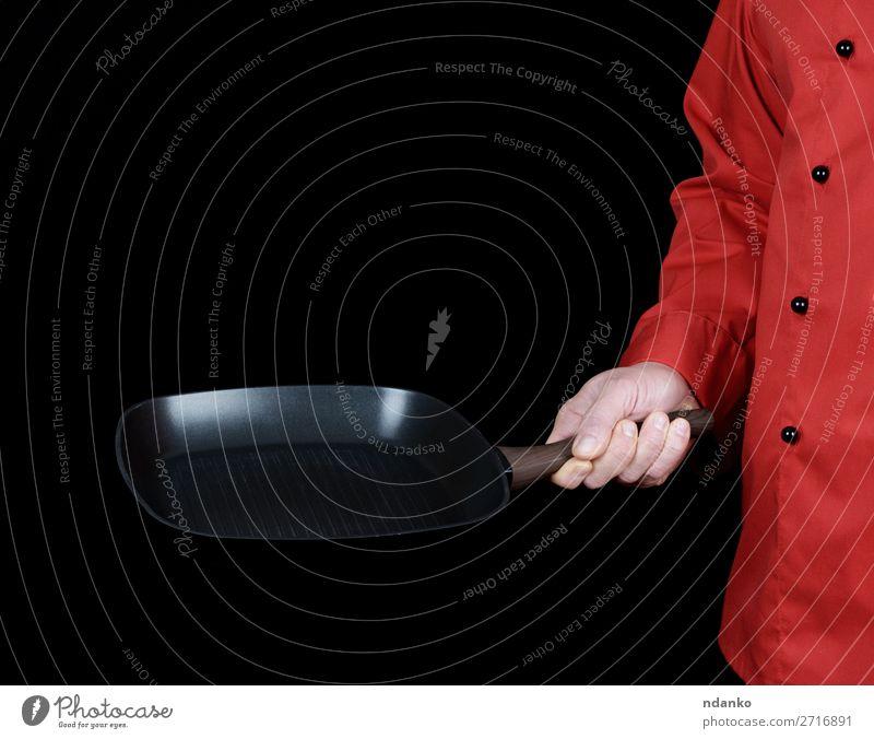 in roter Uniform kochen und eine Bratpfanne halten Pfanne Küche Restaurant Koch Mensch Mann Erwachsene Hand Bekleidung schwarz Gußeisen Kaukasier Küchenchef