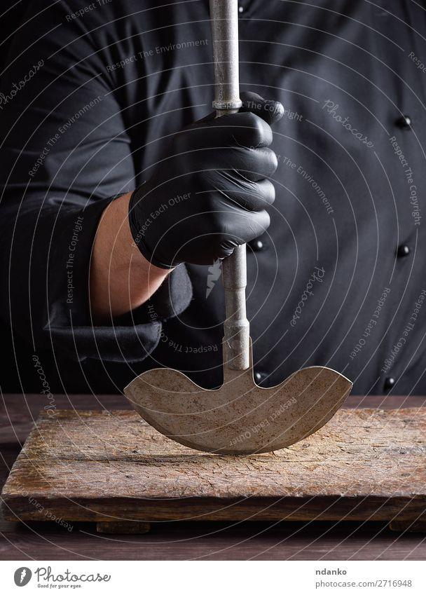 Chefkoch in schwarzer Kleidung hält Metall altes Messer fest Küche Arbeit & Erwerbstätigkeit Koch Mann Erwachsene Hand Handschuhe Stahl machen groß Klinge