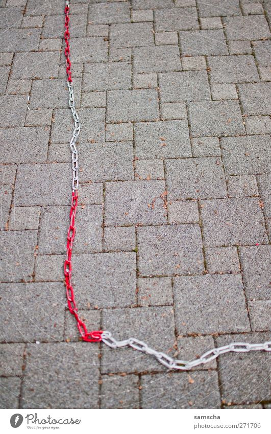 Kettenglieder Stadt Stadtzentrum Platz Marktplatz Verkehr Autofahren Stein hängen fest grau rot weiß Freiheit Kontakt Sicherheit Verbote Barriere schließen