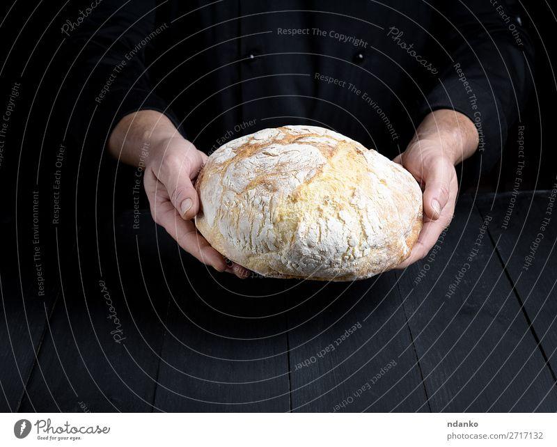 männliche Kochhände halten einen ganzen Laib gebackenes Rundbrot. Brot Ernährung Tisch Küche Mensch Mann Erwachsene Hand Holz machen dunkel frisch braun schwarz