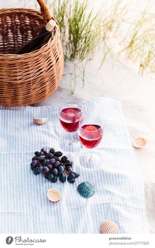 Zwei Weingläser, Trauben, Weidenkorb am Strand Lebensmittel Frucht Picknick Getränk Alkohol Champagner Flasche Sektglas schön Erholung Ferien & Urlaub & Reisen