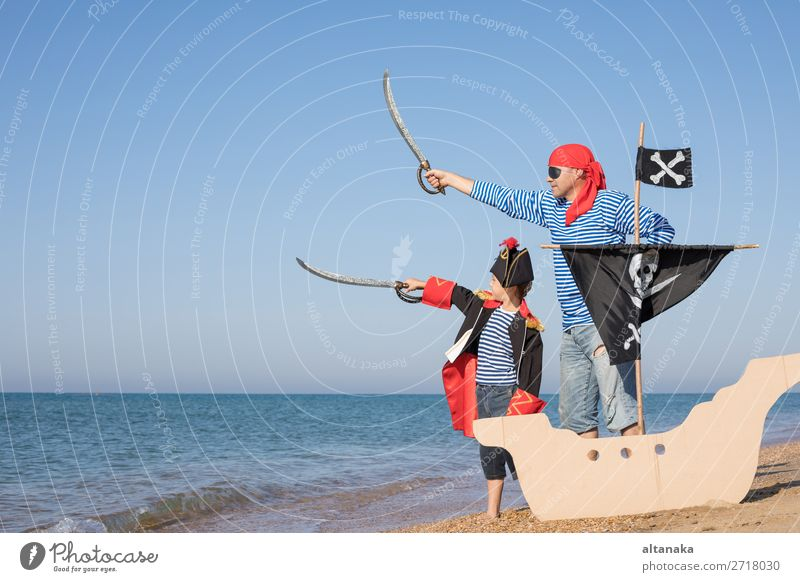 Vater und Sohn spielen zur Tageszeit am Strand. Sie sind mit Matrosenwesten und Piratenkostümen bekleidet. Konzept des glücklichen Spiels im Urlaub und der freundlichen Familie.