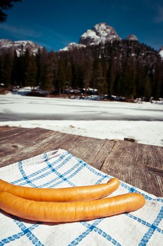 2 Wiener in Tirol Lebensmittel Wurstwaren Ernährung Mittagessen Picknick Schnee Berge u. Gebirge Tisch Umwelt Natur Landschaft Himmel Schönes Wetter Holz liegen