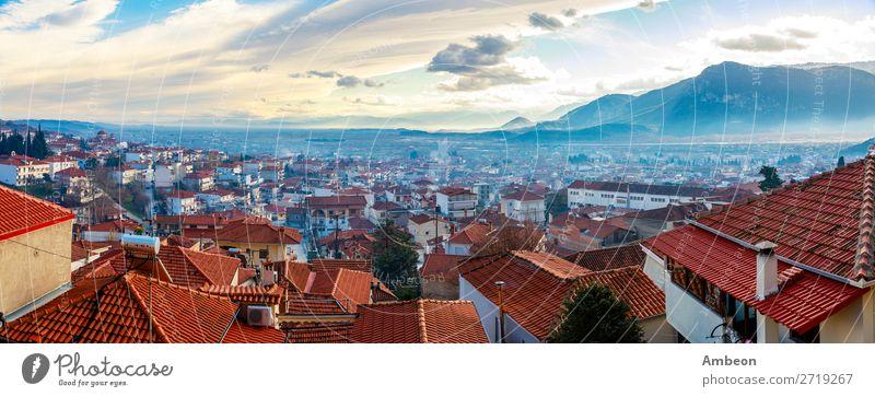 Griechisches Stadtabendpanorama mit Häusern mit roten Dächern im Tal mit Bergen im Sonnenuntergang, Kalabaka, Thessalien, Griechenland Herbst schön Gebäude