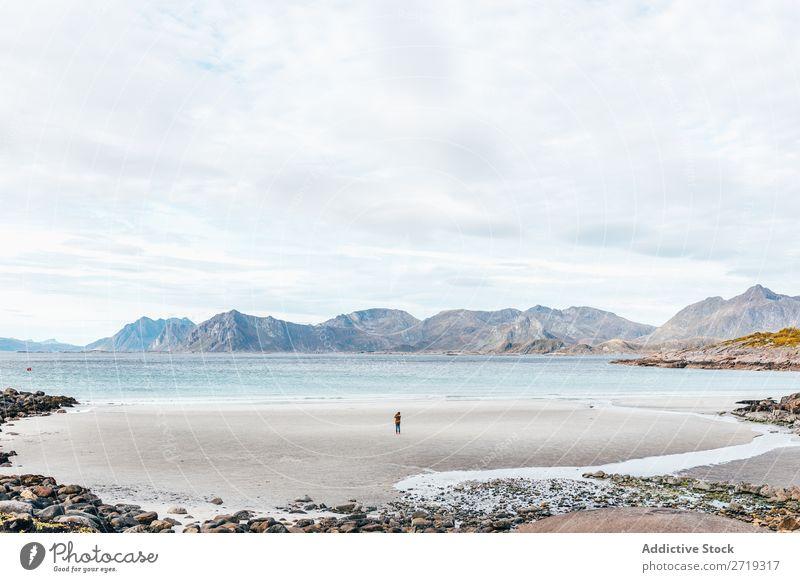 Anonyme Person, die auf dem Meer steht. Wellen Küste See Wasser Hügel Berge u. Gebirge Gipfel