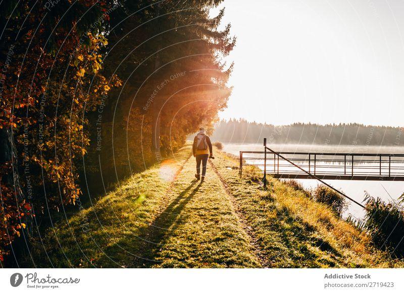 Backpacker im Morgenlicht am Seeufer ruhig mehrfarbig Landschaft Gold Küste Freiheit