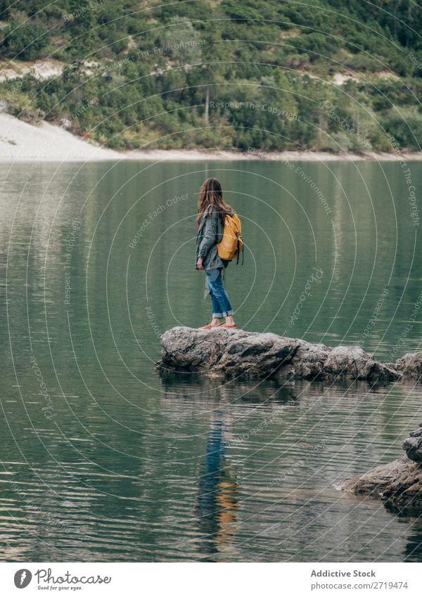 Backpackerin auf Stein im See Frau Rucksack Berge u. Gebirge Tourismus Landschaft Aktion Freiheit Tourist Abenteuer Natur Körperhaltung Wasser Rippeln