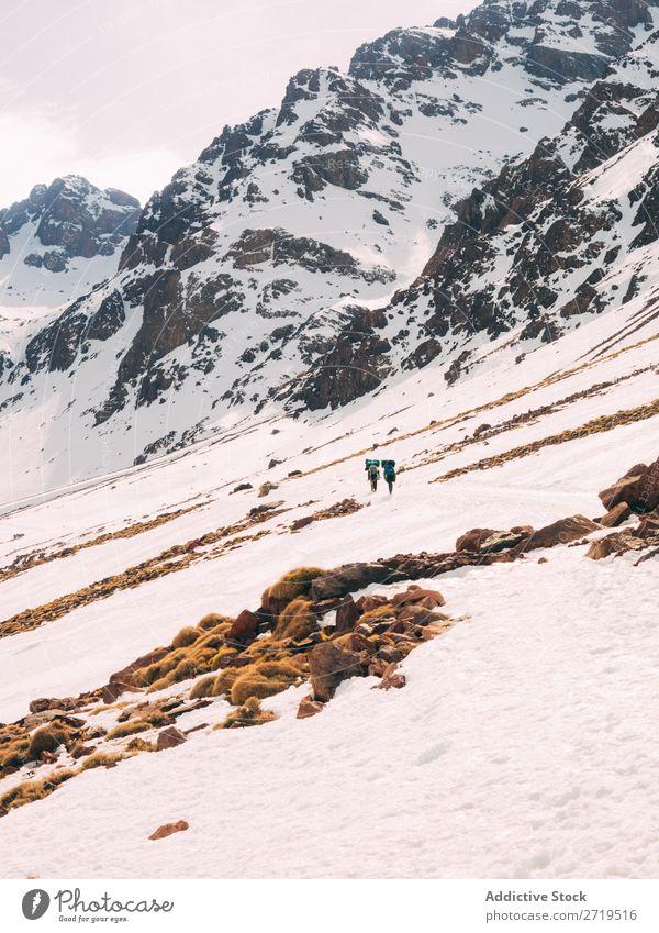 Menschen, die auf einem verschneiten Hang der Berge wandern. Berge u. Gebirge Tourismus Winter Landschaft Felsen Schnee