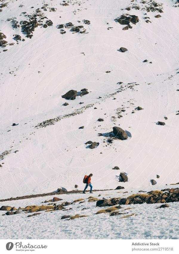 Person, die im Schnee in den Bergen wandert. Mensch Berge u. Gebirge Tourismus Winter Landschaft Felsen Abfahrt