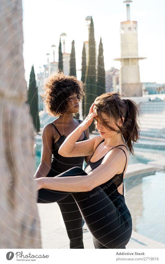 Frauen, die ihre Beine im Park ausstrecken. sportlich Zusammensein hübsch Jugendliche heiter Lächeln Dehnübung Teich Großstadt schön multiethnisch