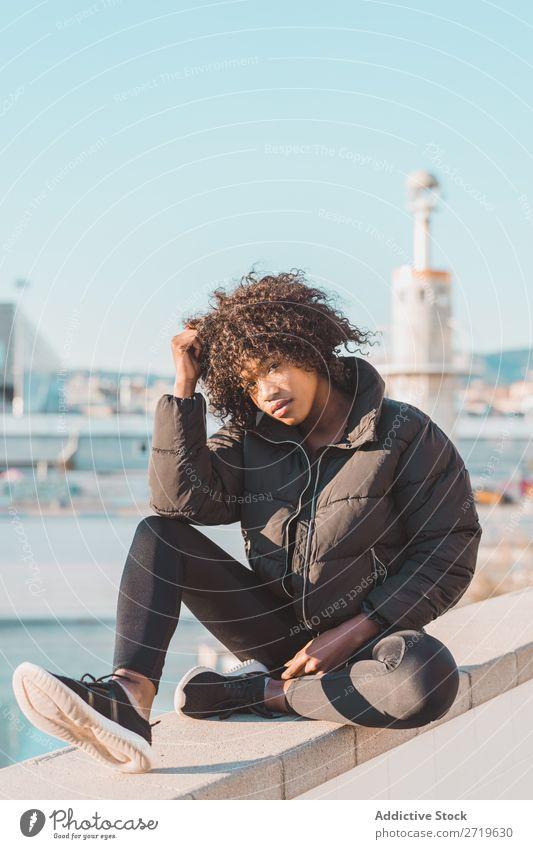 Stilvolle Frau auf dem Zaun sitzend urwüchsig hübsch schön Jugendliche Großstadt Park lässig Coolness Porträt Mensch attraktiv lockig schwarz Gesicht