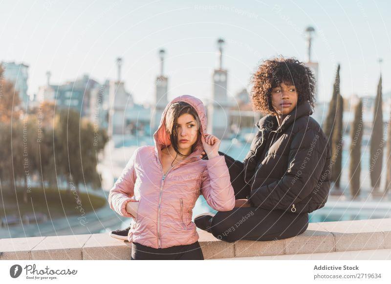 Fröhliche Frauen, die am Zaun posieren. schön Jugendliche Teich Park Coolness Großstadt Stadt