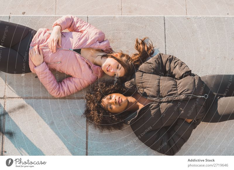 Frauen, die auf der Straße auf dem Boden liegen. schön Jugendliche Park Blick in die Kamera lügen Coolness