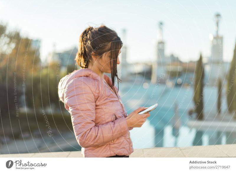 Hübsche Frau steht mit Smartphone auf der Straße. hübsch PDA Park Glück schön Telefon Jugendliche Mobile attraktiv Lifestyle Natur Außenaufnahme heiter Porträt
