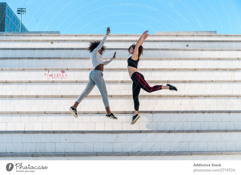 Hübsche, fitte Frauen, die zusammen springen. sportlich Zusammensein hübsch Jugendliche heiter Lächeln Freitreppe strecken schön Sport multiethnisch