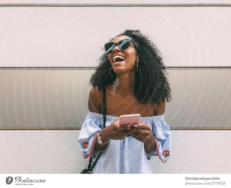 Fröhliche schwarze Frau mit Handy Wand Erwachsene lässig PDA Afrikanisch urwüchsig