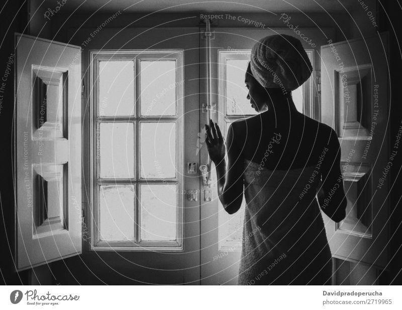 Eine Frau, die in ein Handtuch gehüllt ist und durch ein altes Fenster schaut. schwarz Erwachsene Hintergrundbild Beautyfotografie attraktiv Fürsorge